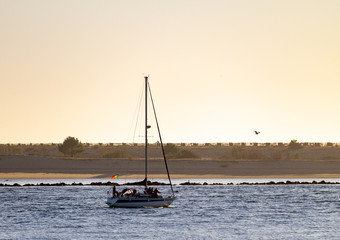 Sailboat Along the River at Dusk