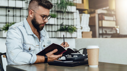 Young bearded hipster man sits in cafe at table, writes in notebook. On table closed laptop, cup of coffee, camera.