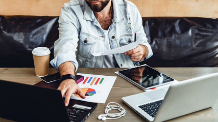 Bearded hipster businessman is working on two laptops in modern office.Man uses computer to enter data. Online marketing