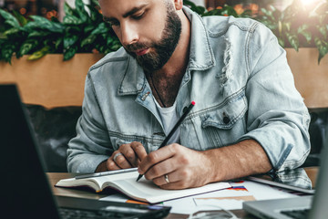 Serious bearded hipster man sitting in office, making notes in notebook, working. Entrepreneur analyzes information.