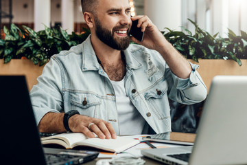 Bearded cheerful man is sitting at table in front of laptops, talking on phone. Freelancer has telephone conversations.
