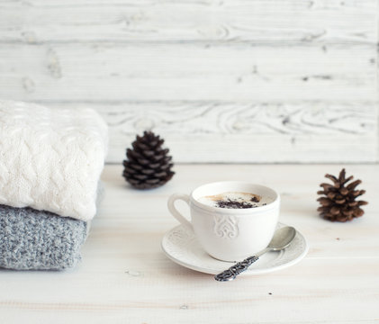 Winter still life with wool clothes, cup of coffee and pine cones