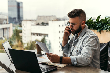 Bearded businessman hipster talking on phone while sitting at desk in office, sad looking at documents. Fall in profits.