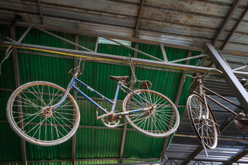 Unused old and dusty retro bicycle hanging under metal roof of home background.
