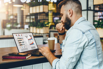Young bearded man is sitting in cafe, typing on laptop with charts,graphs,diagrams on screen. Businessman works in cafe.