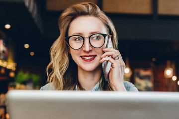 Portrait businesswoman in glasses sitting in cafe in front of laptop,talking on phone.Girl blogger communicates by phone
