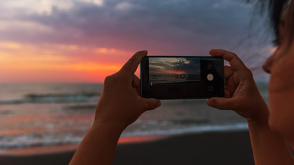 Girl takes pictures on smartphone dawn on the sea