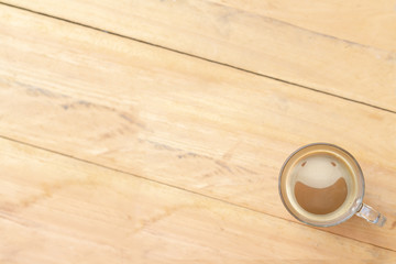 Top view picture of clear glass coffee cup with smiling face from creamy coffee froth put on the mirror table and blurry wooden floor. Selective focus and copy space.