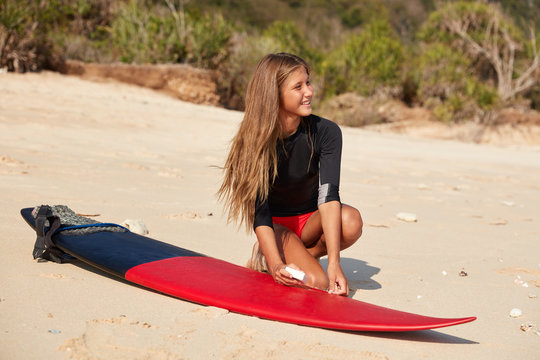 Beautiful cheerful surfing girl waxes surfboard with wax, prepares for real collasping waves, poses on empty beach, has pleasant appearance, looks aside happily. Healthy lifestyle, vacation, hobby