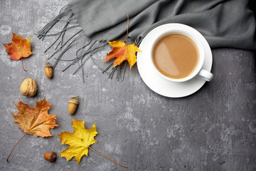 Autumn composition. Cup of coffee, blanket, autumn leaves on grey background. Flat lay, top view.