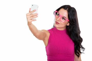 Studio shot of young beautiful Spanish woman taking selfie pictu