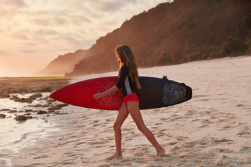Sideways shot of healthy woman in red bikini, walks on sandy beach, carries surfboard, has outdoor summer activities, going to fight current, has physical activity, recreates in nature near ocean