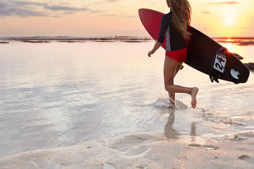 Back view of running girl surfer in swimsuit, carries board under arm, ready to conquer giant wave, runs into ocean, beautiful panoramic view, sunset, wet sand with left footrpint on surface