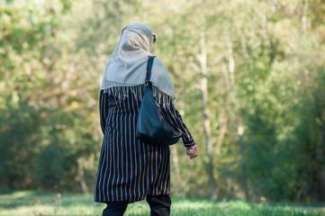Portrait of Veiled Muslim woman walking in public garden on back view