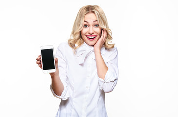 Gorgeous excited woman showing blank screen mobile phone over white background, celebrating victory and success. Very excited, cheering emotion.