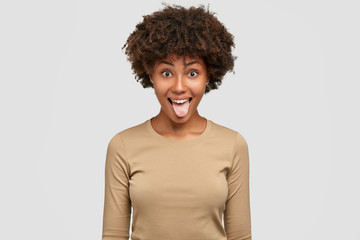 Studio shot of funny black woman shows tongue, has playful expression, Afro hairstyle, makes grimace, dressed in casual beige sweater, isolated over white background. Comic dark skinned girl