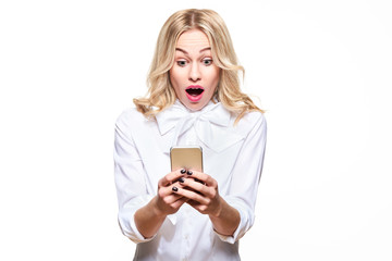 Shocked young woman looking at her mobile phone, screaming in disbelief. Woman staring at shocking text message on her phone, isolated over white background.