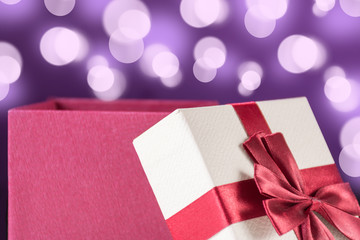 Red opened gift box with bow and purple background with bokeh. Christmas and holiday present concept. Close up, selective focus