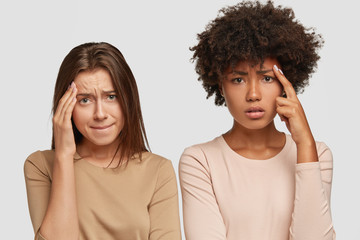 Sad dejected stressful young women have headache, keep hands on foreheads, have displeased expressions, dressed casually, isolated over white background, feel down, press lips. Horizontal shot