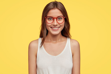 Horizontal view of cheerful emotive brunette girlfriend in optical glasses and white vest, has positive smile on face models over yellow background. Satisfied journalist has great news for publication