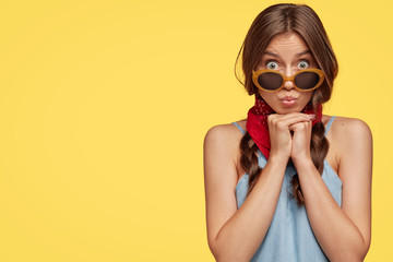 Photo of surprised brunette woman rounds lips, makes funny expression, stares through sunglasses, dressed in denim t shirt, stands against yellow background, free space for your advertisement