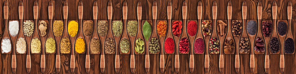 Spices and herbs from different countries in wooden spoons. Colorful seasonings on   table background, top view.