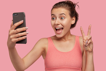 Horizontal view of cheerful European woman makes peace gesture at camera of cell phone, dressed in pink vest, being in good mood, shares photos in social networks, poses for selfie indoor, isolated