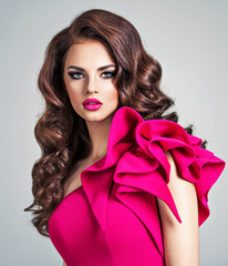 Woman wearing fashionable and creative red dress with a creative hairstyle.