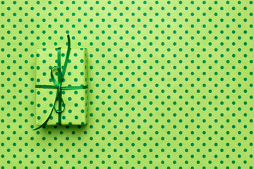 Green gift box on wrapping paper with polka dots. Minimal background with copy space. Holidays concept.