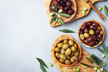 Marinated olives in bowls on kitchen board from olive wood top view.
