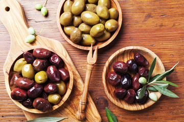Natural greek olives in bowls with kitchen board from olive tree from above.