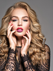 Blond woman with long curly beautiful hair. Makeup. Fashion make-up.