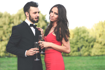 Happy couple of lovers with a glass of wine or champagne standing outdoors in the garden during wedding party or banquet