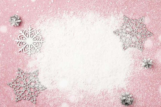 Cherry pink Christmas frame of snow and silver snowflakes. Winter holidays greeting card with copy space. New Year.