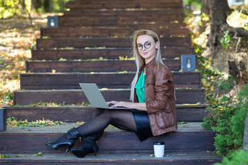 Young freelancer woman using laptop outdoor sitting on steps and smiling at camera. Girl using laptop in the park.