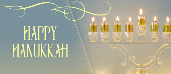 image of jewish holiday Hanukkah background with crystal menorah (traditional candelabra) and candles.