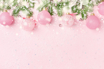 Christmas border of New Year's ornaments, fir and snow on pastel pink. Winter holidays, New Year background with copy space.