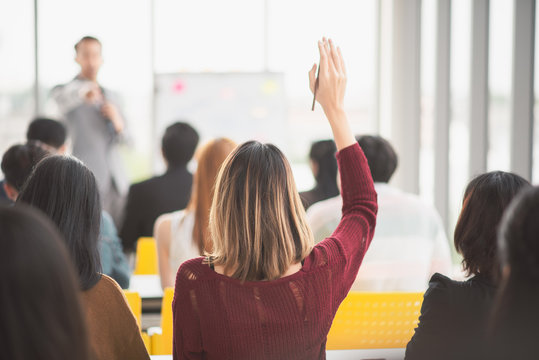 Woman raising up hand for asking the speaker and the speaker point the woman in seminar meeting room back side