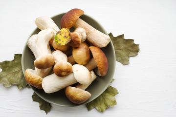 Autumn fresh boletus mushrooms in a plate on a table, close up.