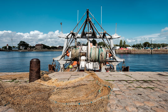 Close-up of fishing nets and fishing boat in a port