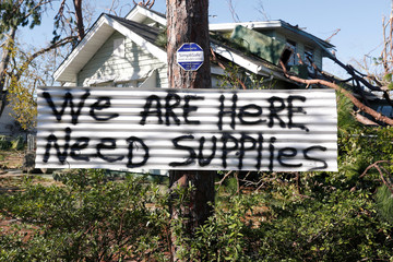 A sign hangs on a tree in front of a house damaged by Hurricane Michael in Panama City