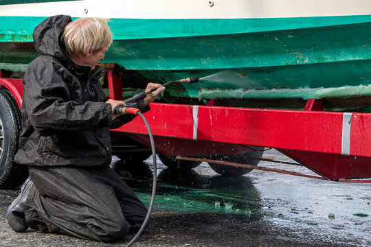 Caucasian man kneeling while high pressure washing dirty boat hull on red trailer