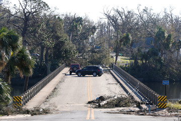 Drivers turn around on a bridge blocked by debris in the aftermath of Hurricane Michael in Panama City