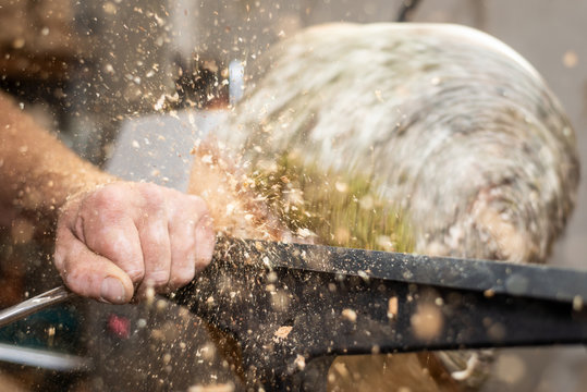 flying wooden sawdust shavings while creating timber bowl on turnery