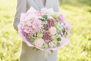 Young girl holding a beautiful spring bouquet. flower arrangement with hydrangea and garden roses. Color light pink. Bright dawn or sunset sun