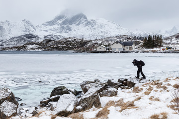 Lofoten islands, Norway. A photographer in the field. Snow and ice, mountains in the background.