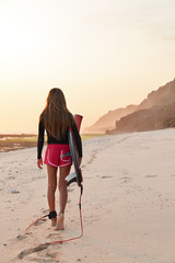 Vertical shot of sporty young woman with sweet buttocks, strolls outdoor, breathes fresh marine air carries surfboard with leash, being tired after fighting wave, connected to board by legrope
