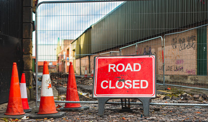 A road closed sign and bollards stop cars from using a road in Sheffield, UK