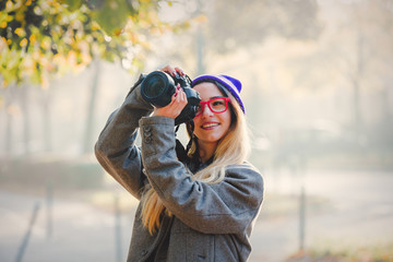 Young girl in glasses and hat with camera on city street.