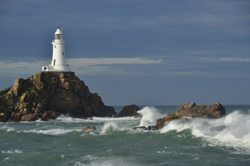 La Corbiere lighthouse, Jersey, U.K. Telephoto image of a stormy coastal landmark.